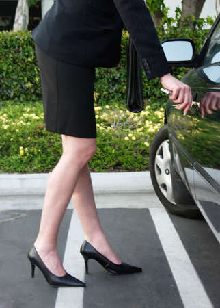 Business woman unlocking car at the end of the day photo