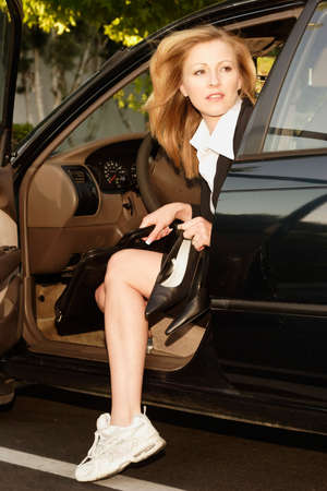 Business woman getting out of car as she arrives at work Stock Photo