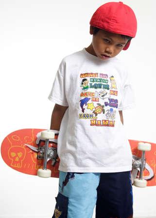 sulk: Sad boy holding a skateboard Stock Photo