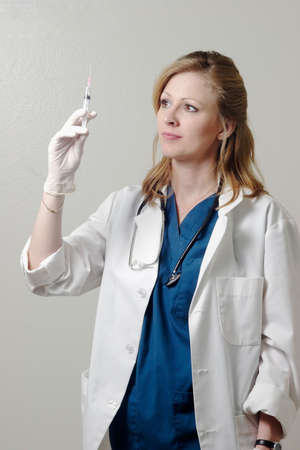 Lady doctor examining syringe Stock Photo