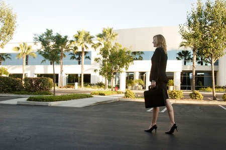 Business woman walking through parking lot carrying briefcase photo