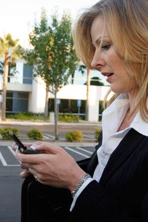 Business woman sending message on blackberry photo