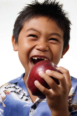 Boy with missing front teeth about to bite an apple Stock Photo - 221838