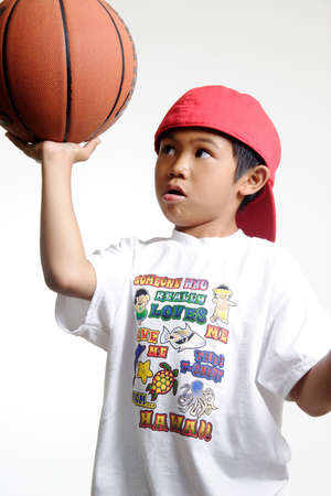 Little boy trying to balance a basketbasll Stock Photo - 222450
