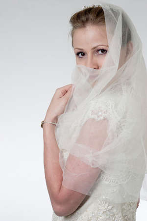 Bride holding veil over face