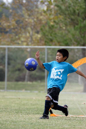 Young boy playing goalie with a big kick photo