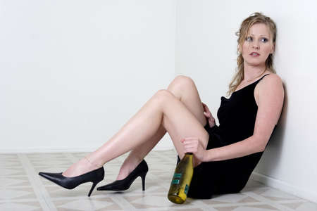drunk woman: attractive blonde woman holding bottle of wine