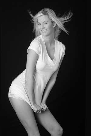 falda corta: Mujer atractiva que intenta sujetar su vestido hacia abajo Foto de archivo