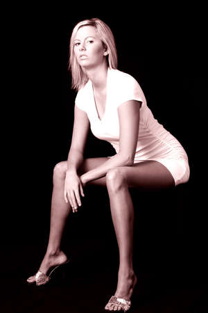 sexy woman sitting on black chair on black background photo
