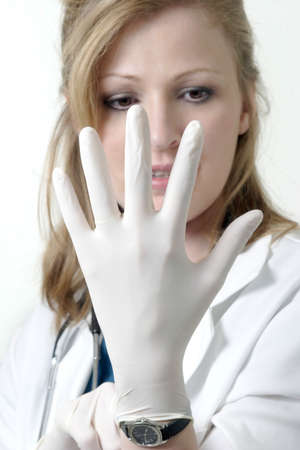 Lady doctor focusing on hand with a surgical glove Stock Photo