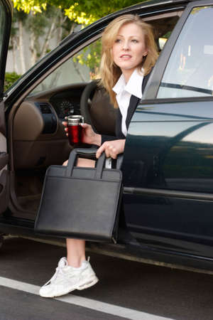 Business woman getting out of car at work Stock Photo