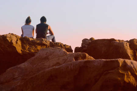 Couple sitting on the rock at sunset Stock Photo - 277862