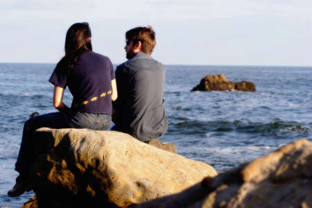 Couple sitting on a rock looking at the ocean Stock Photo