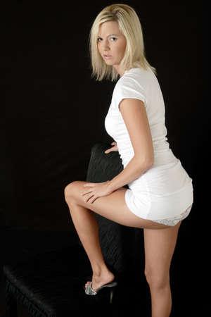 falda corta: Sexy mujer en muy corto vestido con la ropa interior mostrando pisar una silla negro  Foto de archivo
