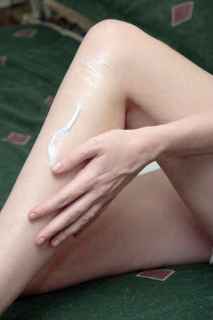 woman's hand rubbing lotion on leg Stock Photo - 285538