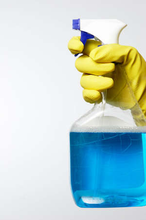 hand wearing yellow cleaning gloves holding a bottle of blue spray cleaner on white Stok Fotoğraf