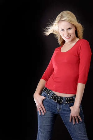wind blown hair: attractive blonde woman in casual red attire with wind blown hair
