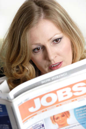 listings: woman reading the job listings in the newspaper
