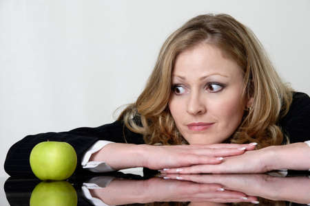 unsatisfied: woman resting chin on hands staring at an apple as if wishing it was something more delicious but needs to watch calories