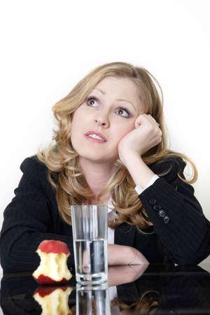vrouw met een appel en water voor de lunch, maar te zoeken als het dromen van iets meer tevreden Stockfoto