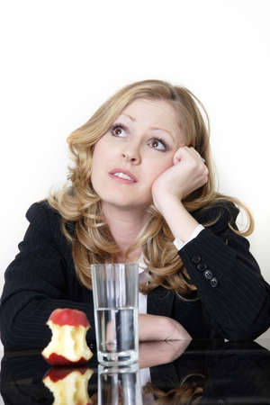 satisfying: woman having an apple and water for lunch but looking up as if dreaming of something more satisfying
