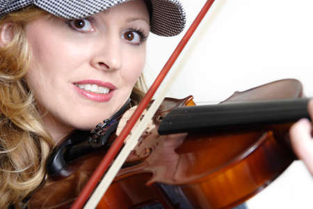 Pretty lady violinist holding a violin with bow on strings up close