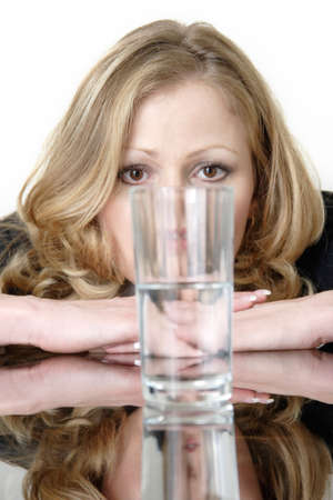 halves: Woman looking intensely at a glass half full or half empty glass of water
