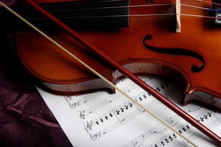 close up of a violin on top of sheet music Stock Photo
