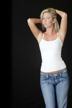 platinum: Blonde woman in jeans and white tank top on black background