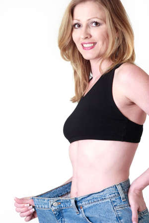 Woman demonstrating weight loss by wearing an old pair of jeans four sizes too big
