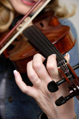 fingering: Woman playing the violin up close focus on the hand and fingers Stock Photo