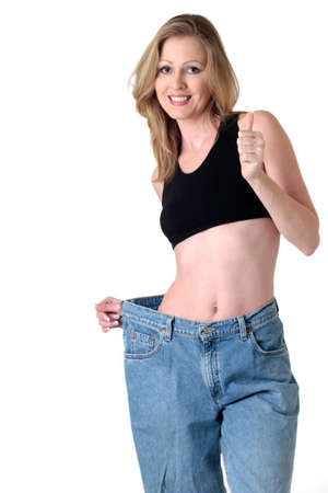 Woman demonstrating weight loss by wearing an old pair of jeans four sizes too big giving thumbs up photo