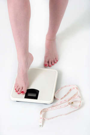 lb: woman stepping onto a bathroom scale with tape measure on the floor