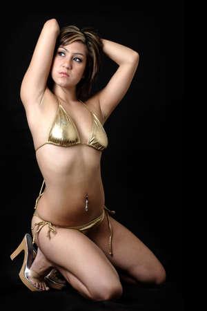 woman kneeling: pretty woman kneeling wearing a gold bikini