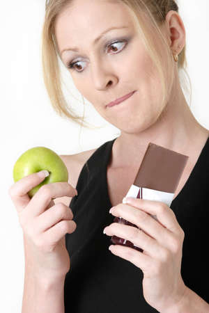 woman holding an apple and chocolate bar trying to decide which one to eat