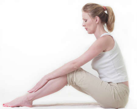 Woman sitting on the floor doing a stretch by reaching for her toes