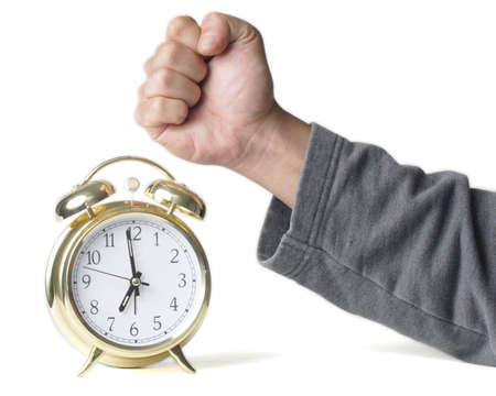 Mans hand in a fist about to hit a gold alarm clock photo