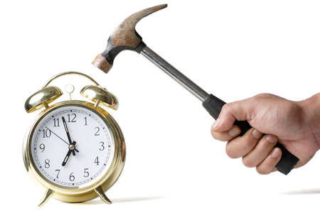 staying in shape: Hand holding a hammer about to hit the alarm clock
