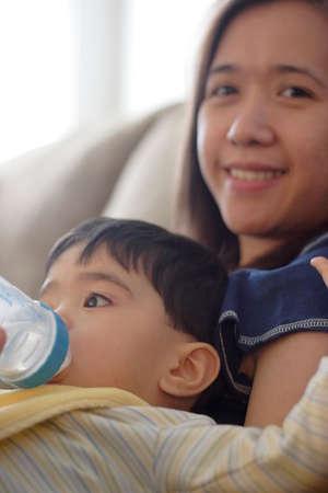Baby drinking bottle while sitting on moms lap Stock Photo