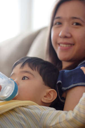 soothe: Baby drinking bottle while sitting on moms lap Stock Photo