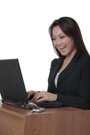 Happy Asian business woman typing on laptop