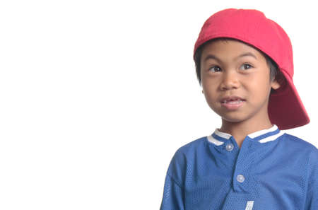 quizzical: Cute young boy in red baseball cap on white with space for copy