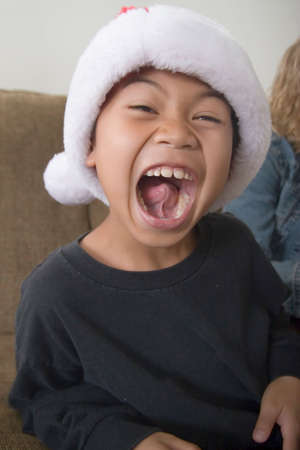 Happy boy in santa hat with mouth wide open showing inside of mouth Stock Photo - 378322