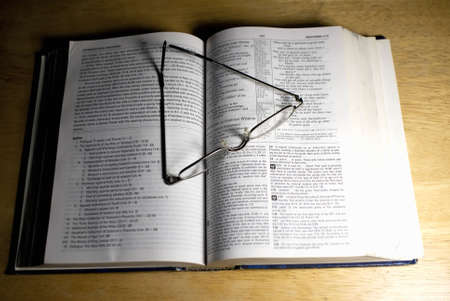 pair of reading glasses on open book