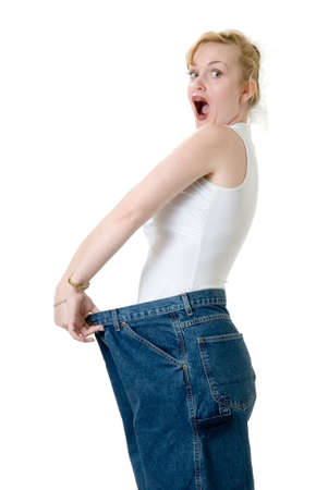Woman demonstrating weight loss by wearing an old pair of jeans four sizes too big and holding them to show off with a shocked expression on her face