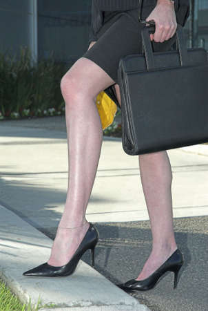 curb: Legs of business woman stepping on a curb