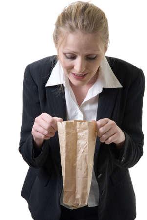 woman at work peeking into lunch bag Stock Photo