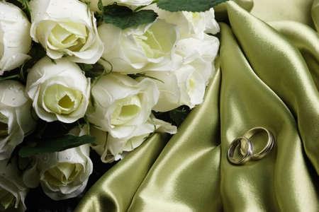 wedding bands: La boda congriega en el sat�n verde con las rosas blancas cerca Foto de archivo