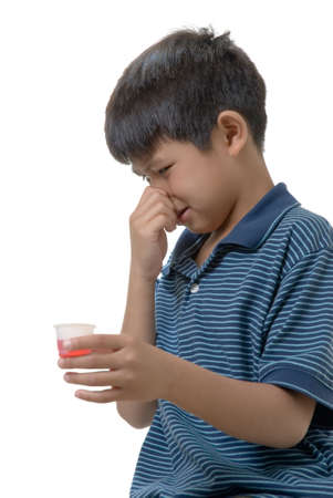 whiff: Cute boy holding nose while holding some pink medicine in a cup Stock Photo