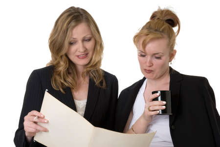 two business women standing looking at file or plans